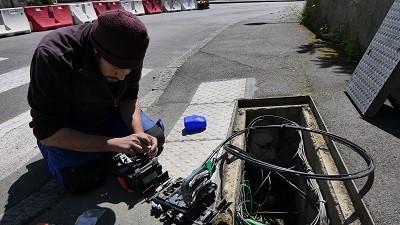 Le technicien raccorde le câble optique de la maison au Point de Branchement Optique.