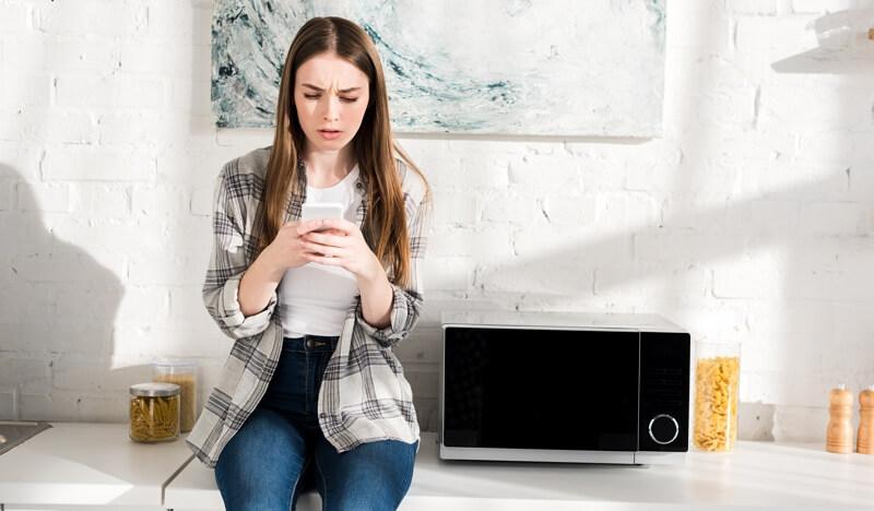 Une jeune femme capte mal le Wi-Fi près de son four micro-ondes
