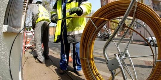 Des techniciens déploient la fibre optique dans une rue