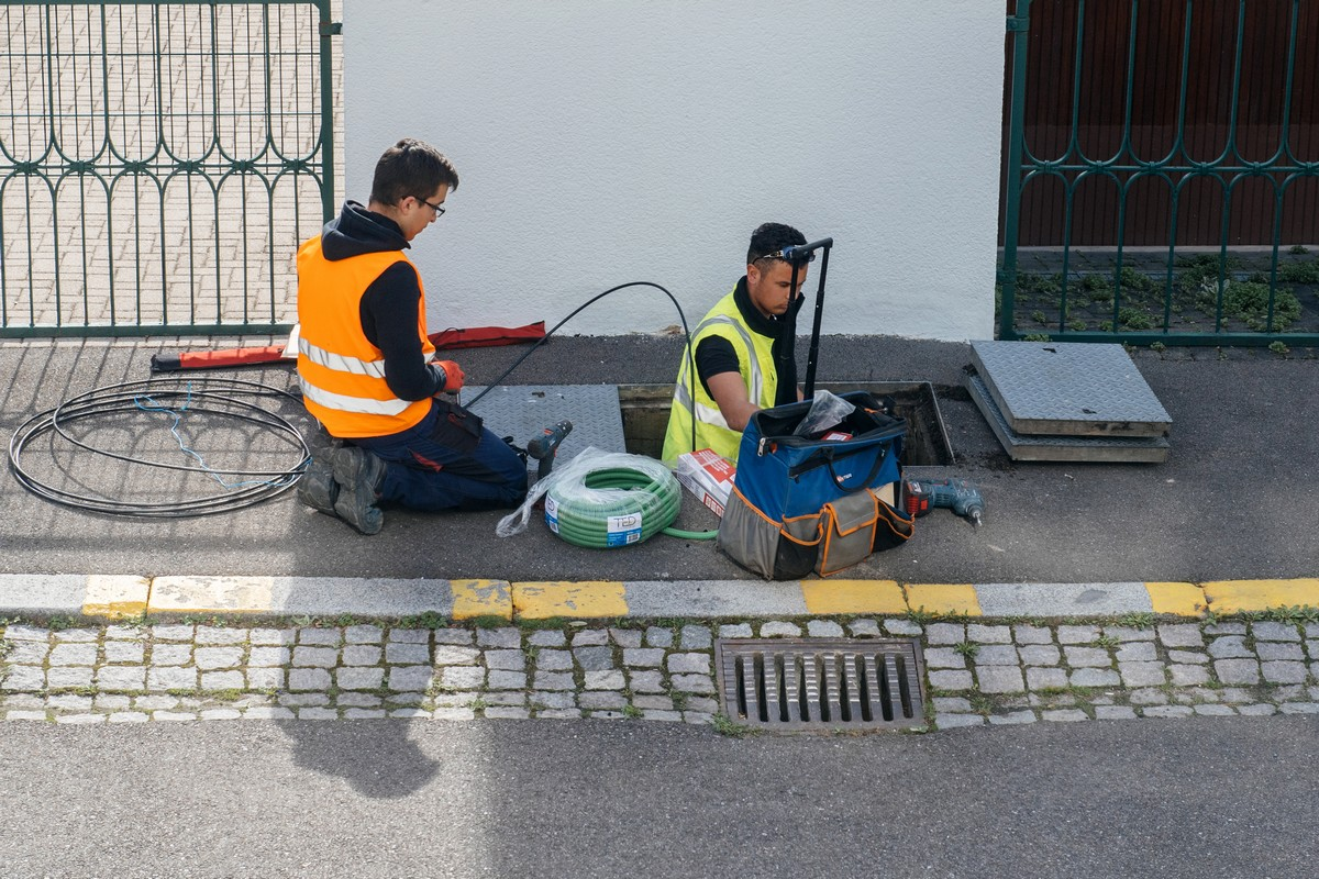 Deux techniciens raccordent un logement au réseau de fibre optique d'Orange