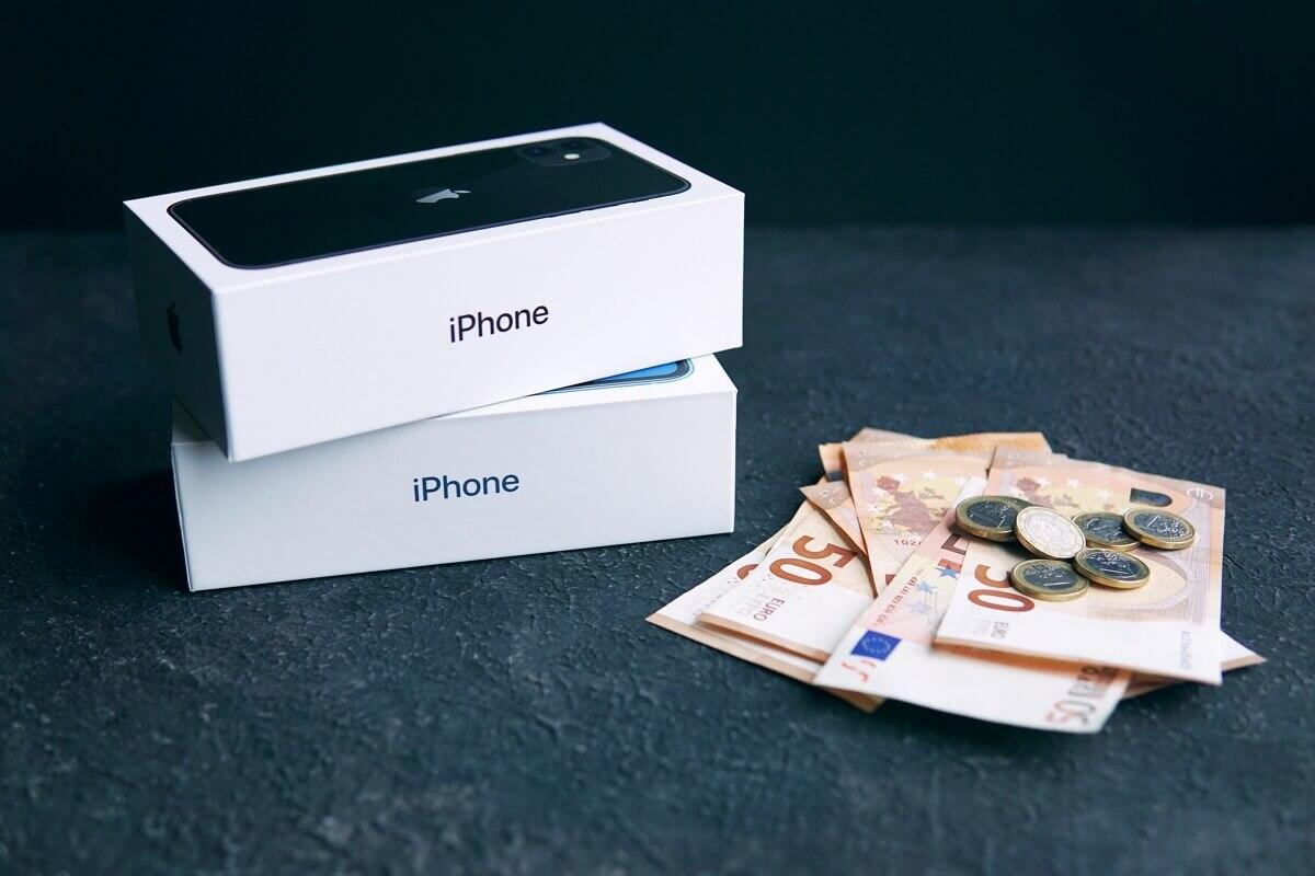 Deux iPhone dans leur boîte à côté de billets de 50 euros