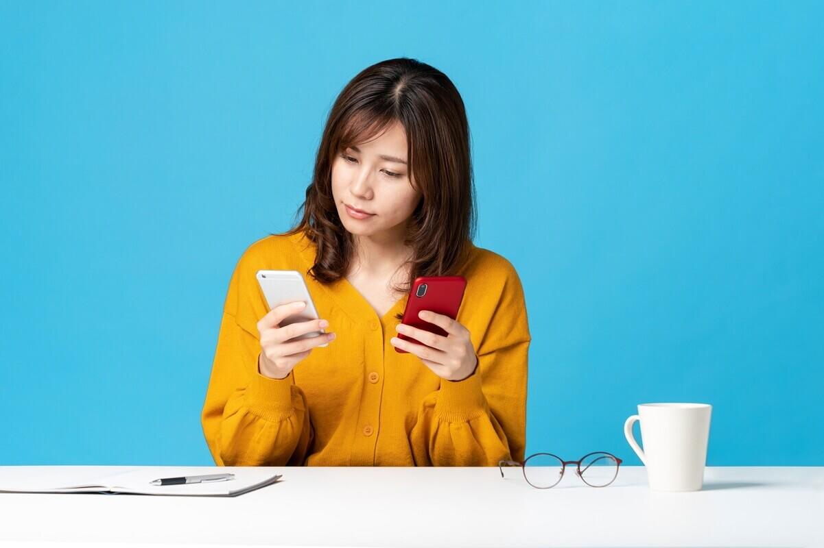 Une jeune femme avec deux téléphones portables