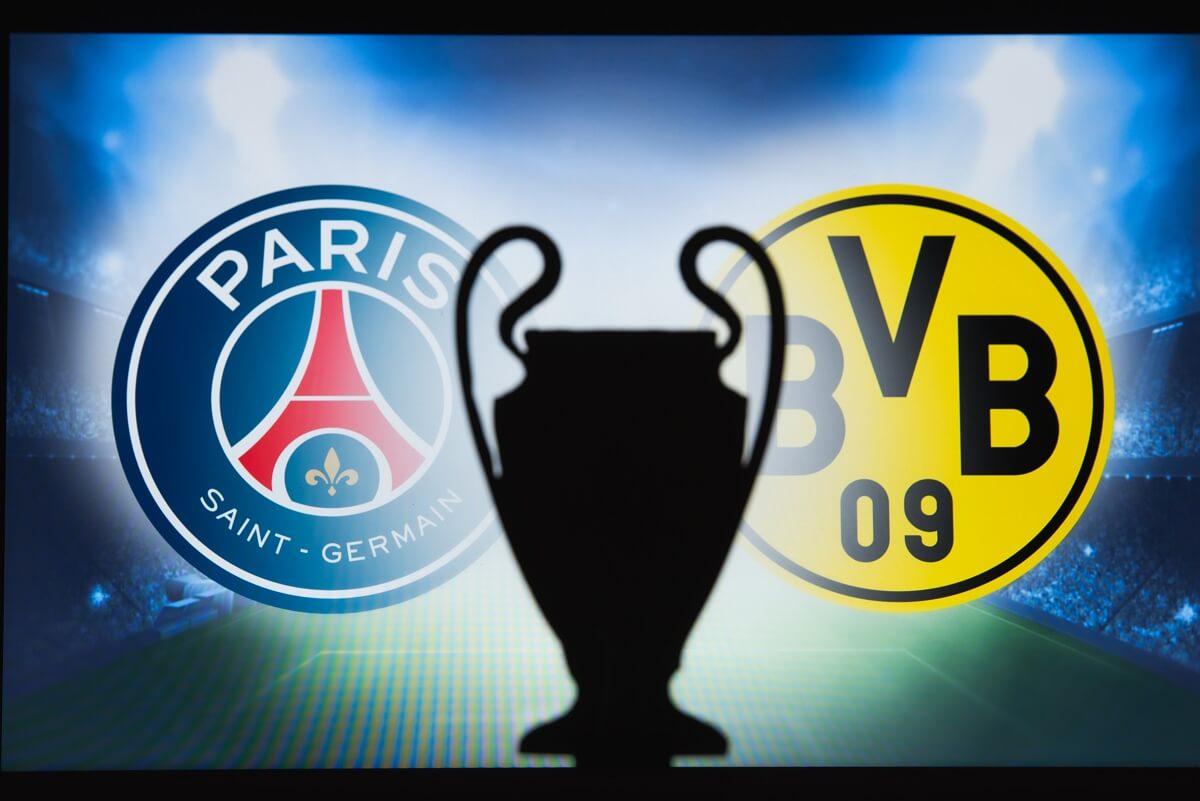 Le trophée de Ligue des Champions entre les emblèmes du PSG et de Dortmund