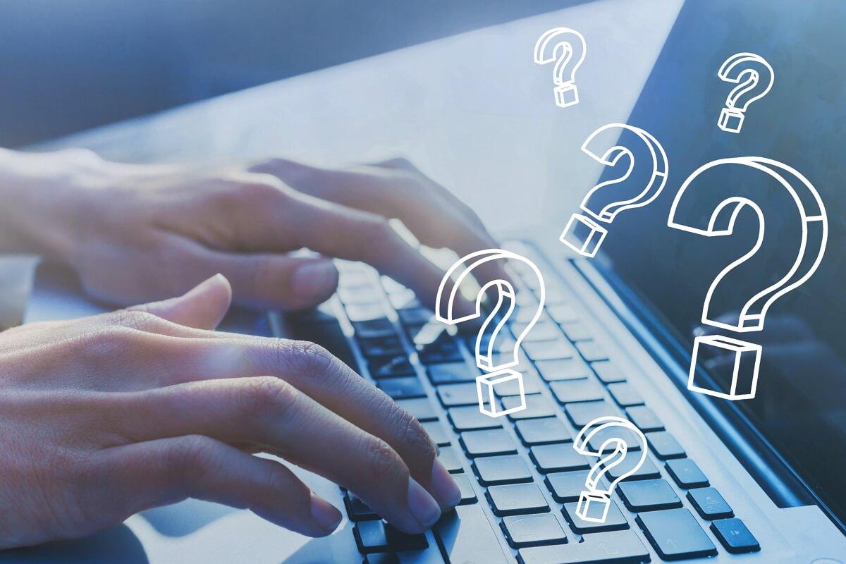 Une personne tape sur son ordinateur, points d'interrogation