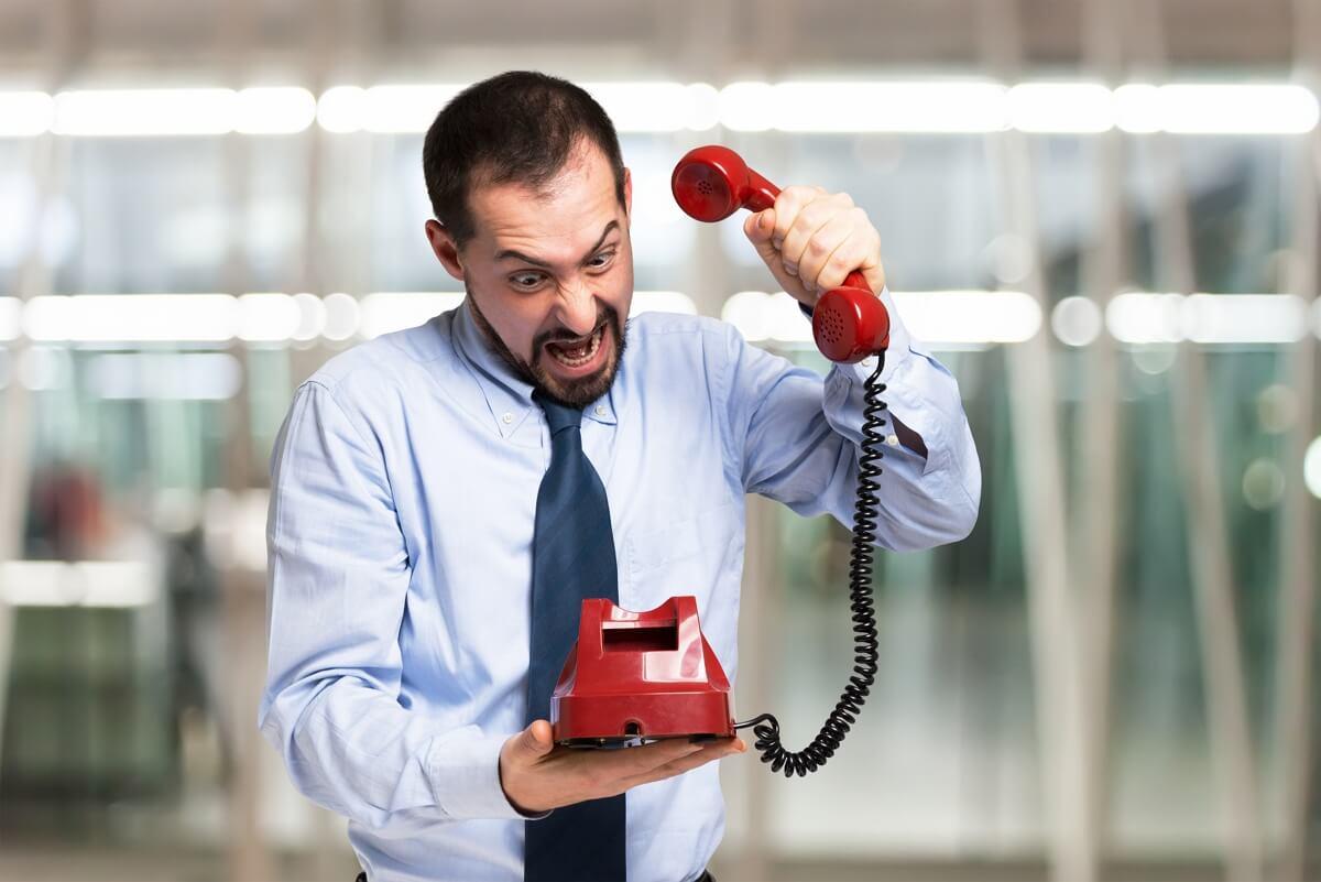 Un homme en colère raccroche son téléphone à cause d'un problème avec son opérateur