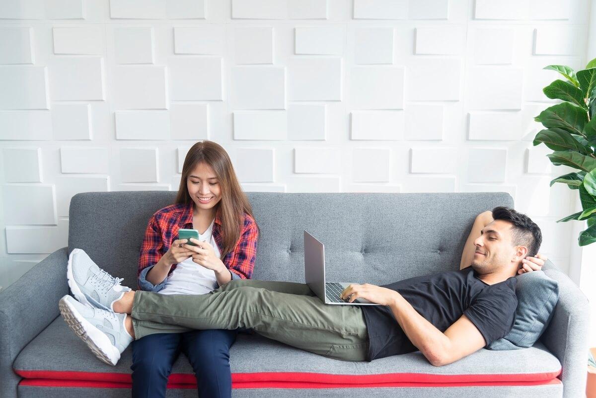 Un couple sur un canapé utilise son abonnement Internet et son forfait mobile