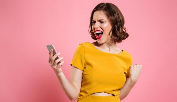 Une femme regarde son téléphone portable avec satisfaction après avoir réalisé un bon plan sur un forfait mobile