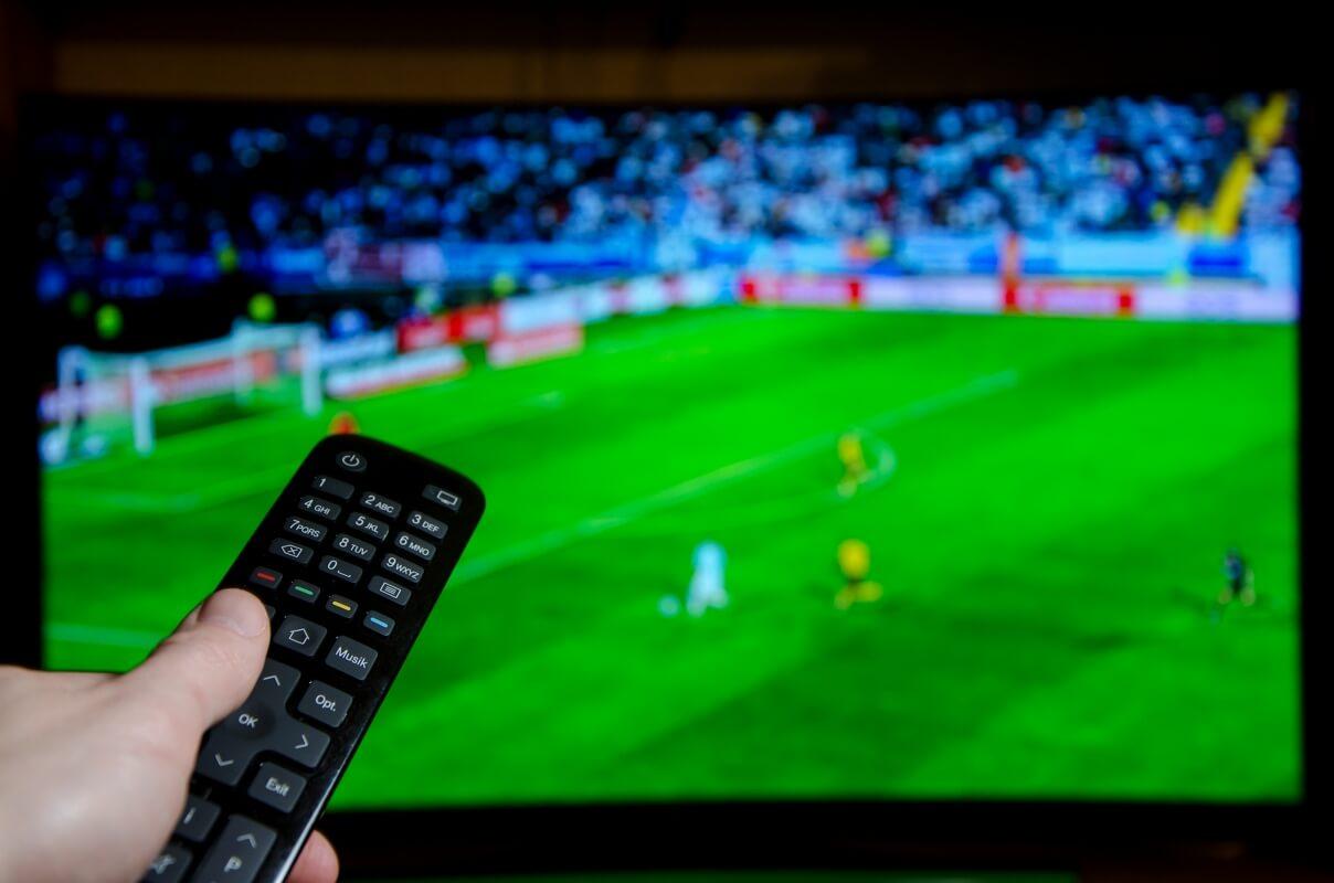 Une personne regarde du foot sur RMC Sport à la télé