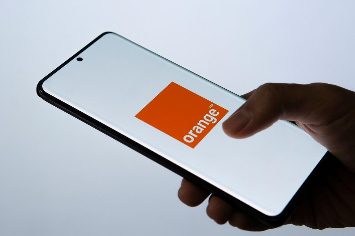 Une personne tient un téléphone Orange à la main
