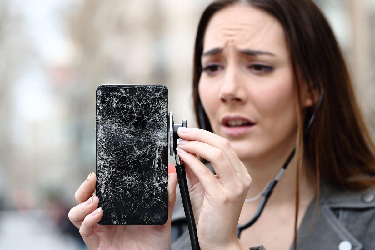 Une femme ne sait pas quoi faire de son téléphone cassé