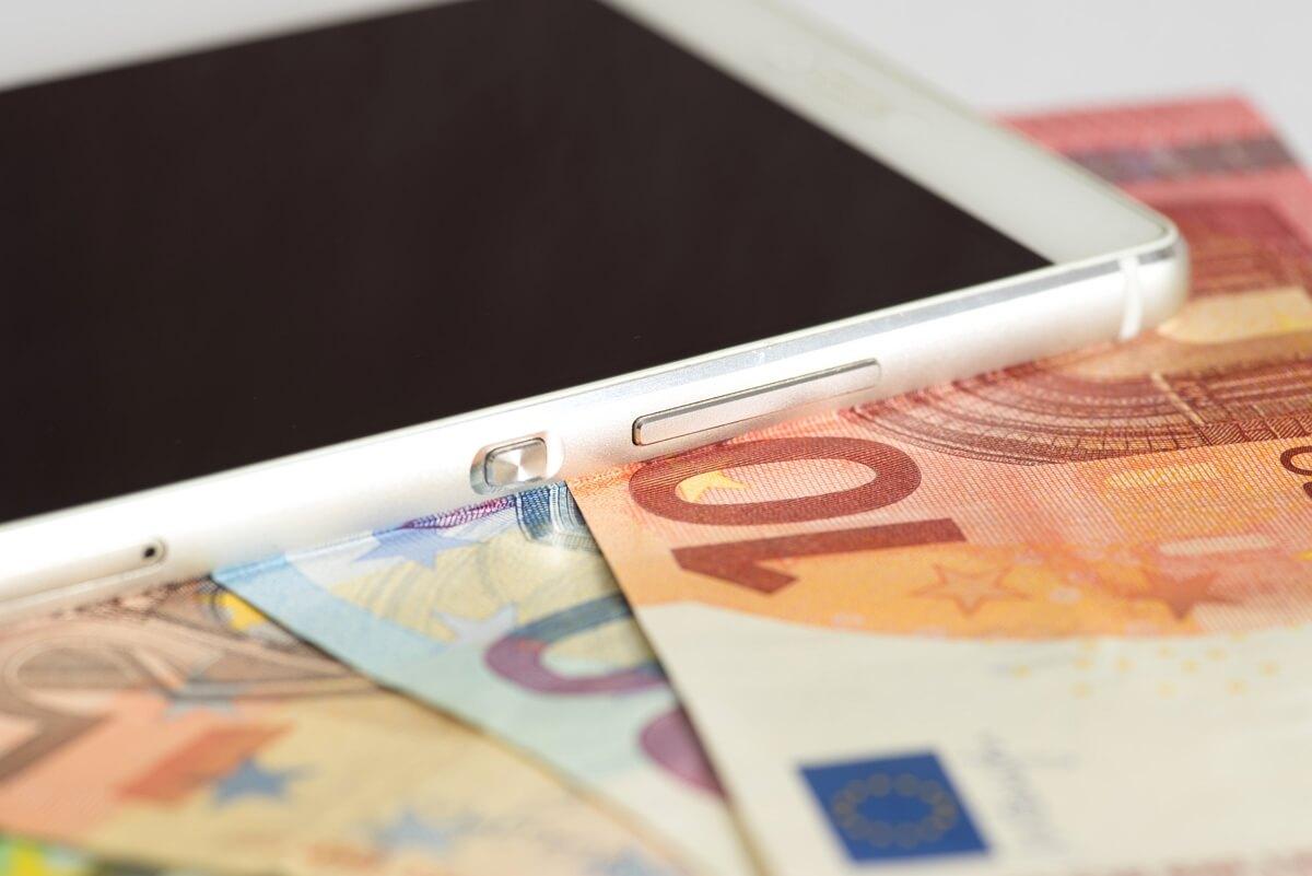 Un téléphone et des billets pour illustrer le prix des forfaits mobiles en 2020